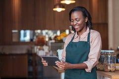 Empresario africano joven sonriente que usa una tableta en su café Fotografía de archivo