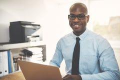 Empresario africano sonriente que trabaja en línea en un Ministerio del Interior fotos de archivo libres de regalías