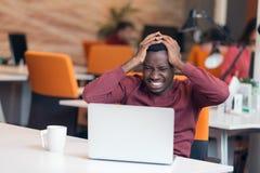 Empresario agotado que trabaja con un ordenador en su oficina fotos de archivo libres de regalías