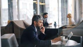 Empresario al hablar en el teléfono móvil y usar el funcionamiento del ordenador portátil en café almacen de metraje de vídeo