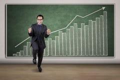 Empresario alegre con el gráfico financiero Imagen de archivo