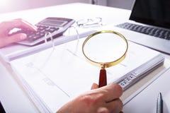 Empresario Analyzing Bill With Magnifying Glass fotos de archivo