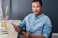 Empresario asiático contento que usa una tableta digital en la oficina foto de archivo libre de regalías