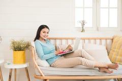 Empresario asiático joven feliz que trabaja con un ordenador portátil en casa Fotografía de archivo