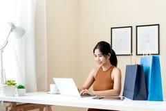Empresario asiático joven que comprueba orden, el correo electrónico o la charla viva con el ordenador portátil en casa Mujer ele imágenes de archivo libres de regalías