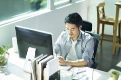 Empresario asiático joven que comtempla en oficina foto de archivo
