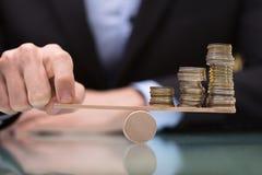 Empresario Balancing Stacked Coins en la oscilación imagenes de archivo