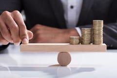 Empresario Balancing Stacked Coins en la oscilación de madera foto de archivo