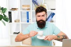 Empresario barbudo del hombre de negocios del encargado del hombre llevar la corona de oro en la cabeza Café de consumición relaj imágenes de archivo libres de regalías