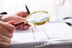 Empresario Checking Bill With Magnifying Glass foto de archivo libre de regalías