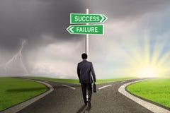 Empresario con el poste indicador al éxito o al fracaso Foto de archivo