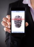 Empresario con el teléfono móvil que explora una huella dactilar foto de archivo