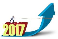 Empresario con la flecha del crecimiento de los tirones de los números 2017 Fotos de archivo libres de regalías