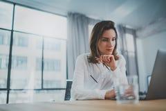 Empresario confiado de sexo femenino usando el ordenador port?til m?vil para mirar una nueva soluci?n del negocio durante proceso imagenes de archivo