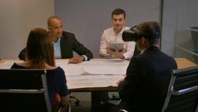 Empresario confiado en vidrios de la realidad virtual Grupo de promotores jovenes que trabajan en dibujos del edificio y del cami almacen de metraje de vídeo
