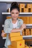 Empresario de la mujer con las cajas del paquete en su propio onl de las compras del trabajo fotos de archivo libres de regalías