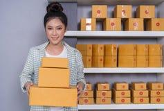 Empresario de la mujer con las cajas del paquete en su propio onl de las compras del trabajo foto de archivo