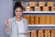 Empresario de la mujer con las cajas del paquete en su propio onl de las compras del trabajo imagenes de archivo