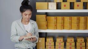 Empresario de la mujer joven que cuenta las cajas del paquete en su propio negocio en línea que hace compras del trabajo