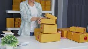 Empresario de la mujer que arregla una caja que se entregará a los clientes almacen de metraje de vídeo