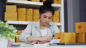 Empresario de la mujer que calcula en casa la oficina financiera, entrega en línea de la caja de embalaje del mercado, pequeño pr almacen de metraje de vídeo