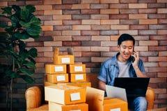 Empresario de negocio de sexo masculino asiático usando el ordenador portátil y el teléfono con los paquetes de cajas en casa fotografía de archivo libre de regalías