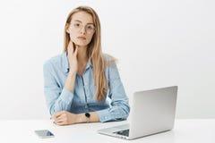 Empresario de sexo femenino acertado en los vidrios y la camisa manual que tocan el cuello como ordenador portátil cercano cansad fotos de archivo libres de regalías