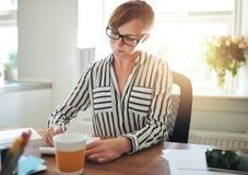 Empresario de sexo femenino acertado que trabaja en casa foto de archivo