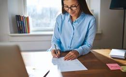 Empresario de sexo femenino acertado que trabaja en su escritorio fotografía de archivo