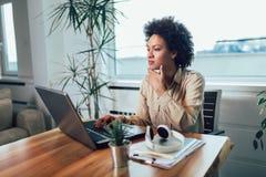 Empresario de sexo femenino africano joven que se sienta en un escritorio en su Ministerio del Interior que trabaja en línea con  fotos de archivo libres de regalías