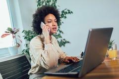 Empresario de sexo femenino africano joven que se sienta en un escritorio en su Ministerio del Interior que trabaja en l?nea con  foto de archivo libre de regalías