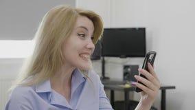 Empresario de sexo femenino alegre sorprendido que recibe buenas noticias en su sensación del teléfono móvil satisfecha y emocion metrajes