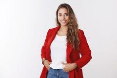 Empresario de sexo femenino ambicioso confiado apuesto de Skillfull que sostiene los bolsillos de las manos que sonríen ampliamen foto de archivo