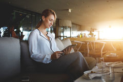 Empresario de sexo femenino joven que lee el libro electrónico en la tableta digital durante almuerzo en interior moderno del res foto de archivo