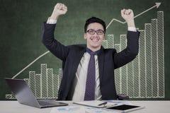 Empresario de sexo masculino alegre con el gráfico de negocio Imágenes de archivo libres de regalías