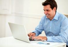Empresario de sexo masculino atractivo que trabaja en su ordenador portátil imágenes de archivo libres de regalías