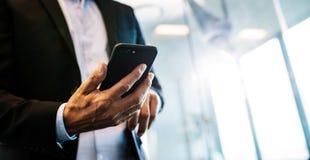 Empresario de sexo masculino con el teléfono móvil en oficina fotos de archivo libres de regalías