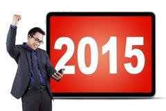 Empresario de sexo masculino con el teléfono móvil y los números 2015 Imagen de archivo libre de regalías