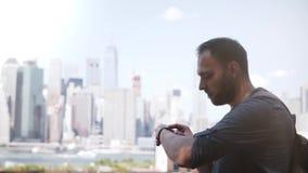 Empresario de sexo masculino confiado feliz que usa la pulsera elegante que se coloca en sorprender el panorama del paisaje urban metrajes