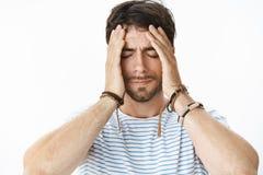 Empresario de sexo masculino difícil ejercido presión sobre con la barba en la camiseta rayada que tiene problemas en el trabajo  imágenes de archivo libres de regalías