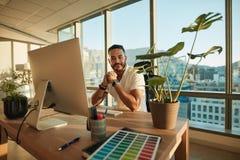 Empresario de sexo masculino hermoso que se sienta en su escritorio imagenes de archivo
