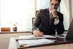 Empresario de sexo masculino que trabaja en su escritorio fotografía de archivo