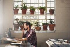 Empresario del diseñador que usa su teléfono mientras que trabaja en lapto imágenes de archivo libres de regalías