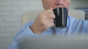 Empresario Drink una taza caliente de café o de té en sitio de la oficina fotografía de archivo libre de regalías