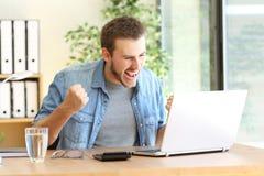 Empresario emocionado con el ordenador portátil en línea fotos de archivo libres de regalías