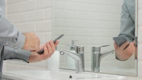 Empresario en cuarto de baño usando su texto del teléfono móvil antes de lavar las manos foto de archivo