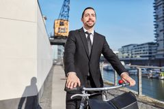 Empresario en el camino con una bicicleta foto de archivo
