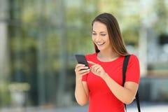 Empresario en rojo usando un teléfono móvil en la calle imagenes de archivo