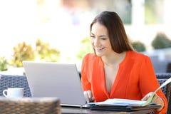 Empresario feliz que trabaja en línea en una cafetería fotografía de archivo