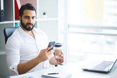Empresario hermoso joven que se sienta en el escritorio y que usa el ordenador portátil adentro imagenes de archivo